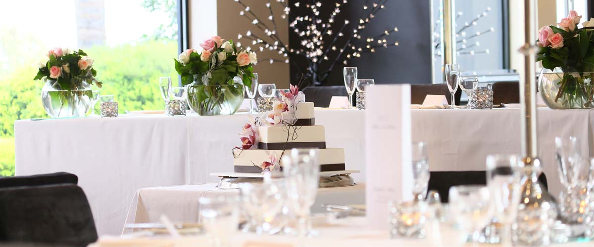 Decorated wedding reception room with tiered wedding cake and flowers