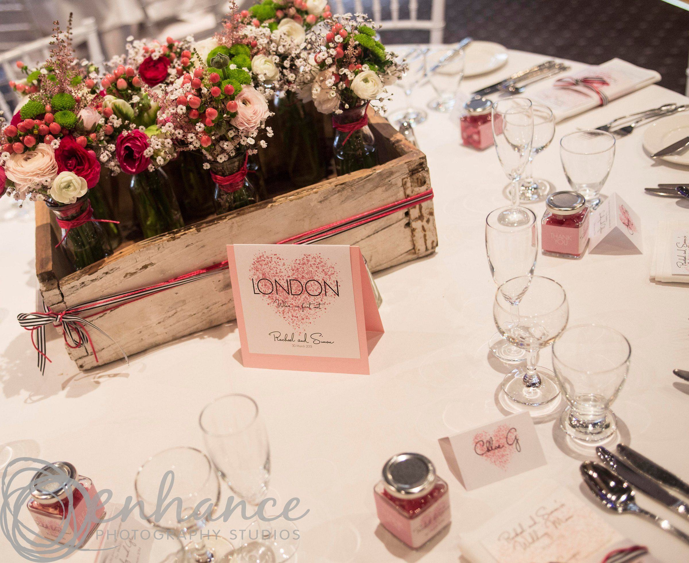 Photo of a table set up for a wedding reception with a wooden box filled with flowers