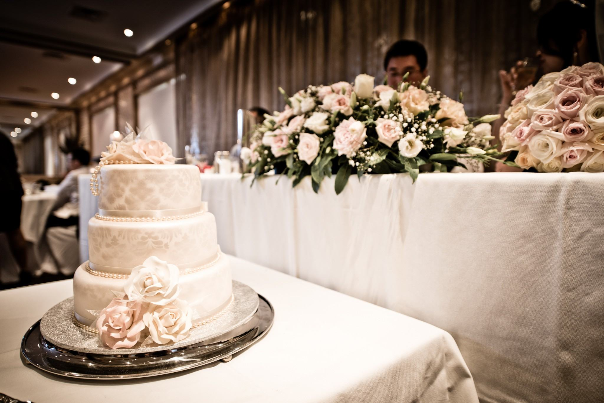 Photo of a decorated wedding cake on a silver platter at a wedding function
