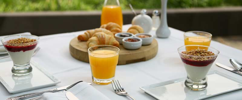 Breakfast table spread with croissants, yoghurt with muesli and orange juice