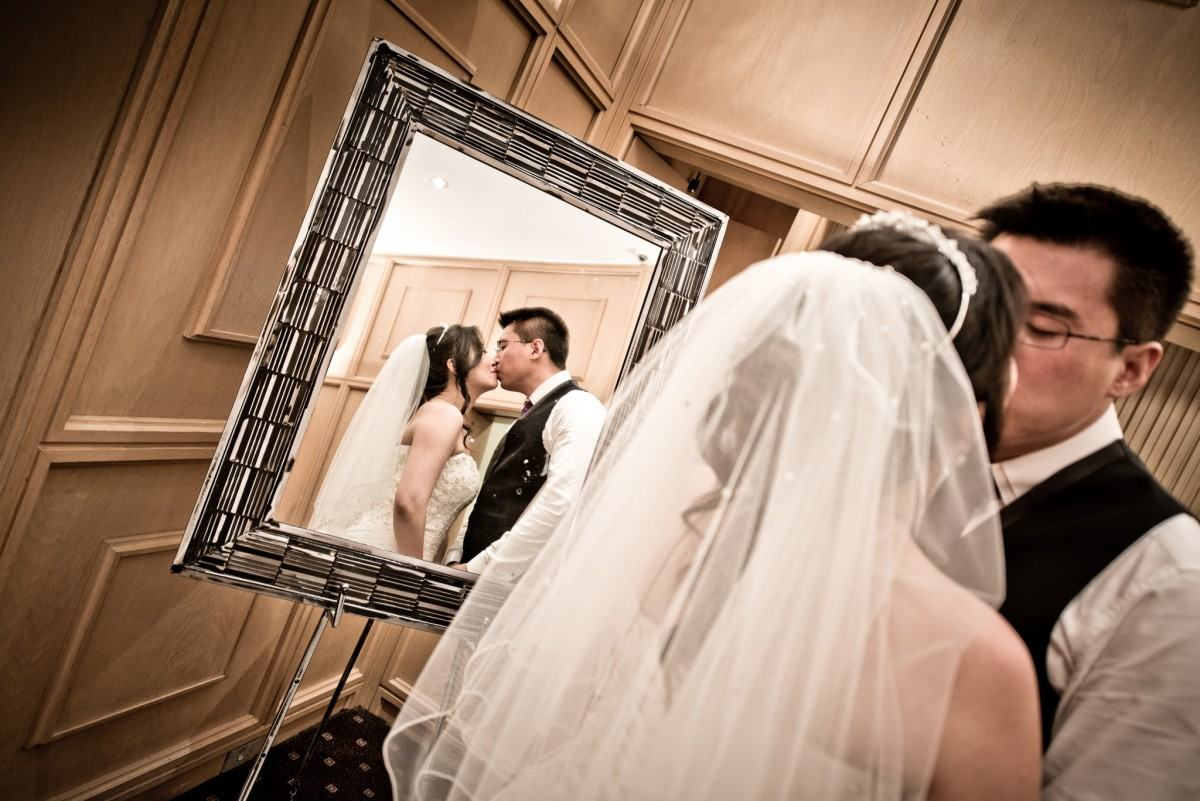 Bride and groom kissing in the mirror