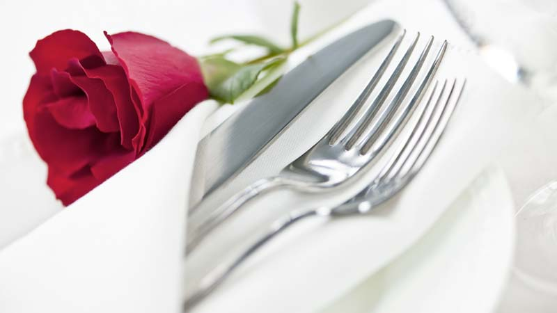 Red rose with silver cutlery wrapped in a napkin